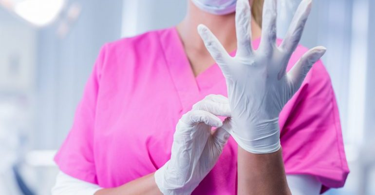 Dentist in pink scrubs putting on surgical gloves at the dental clinic