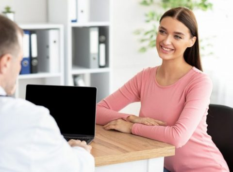 Male experienced doctor talking with female patient