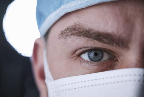 Male healthcare worker in scrubs head shot, close up crop
